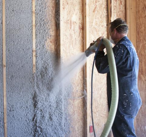 Installation of cellulose insulation in home.