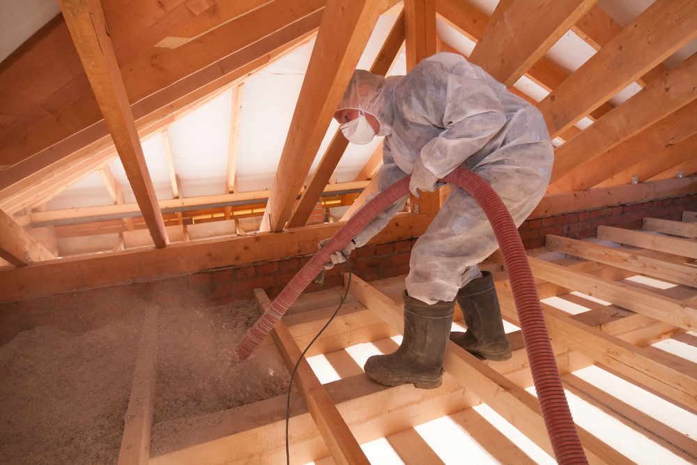 Worker installing cellulose insulation with mask, boots, gloves, and plastic clothing Valley Insulation Home Insulation Safety