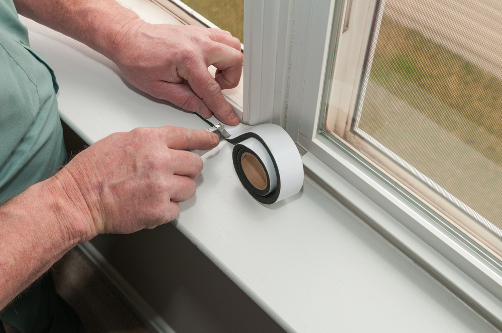 Man's hands installing weather stripping along a window