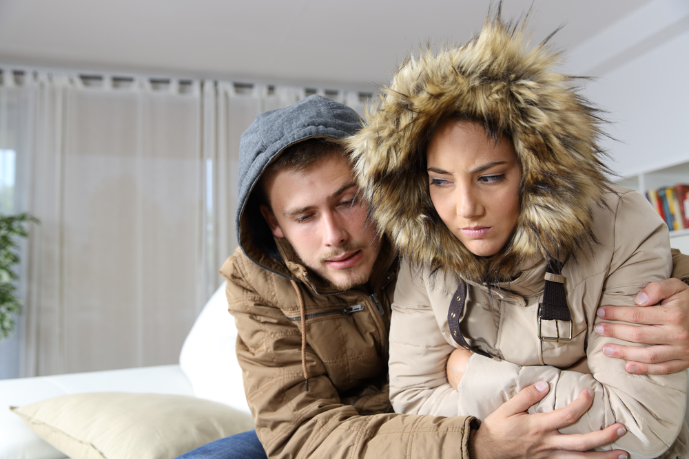Young couple in a cold home bundling for warmth