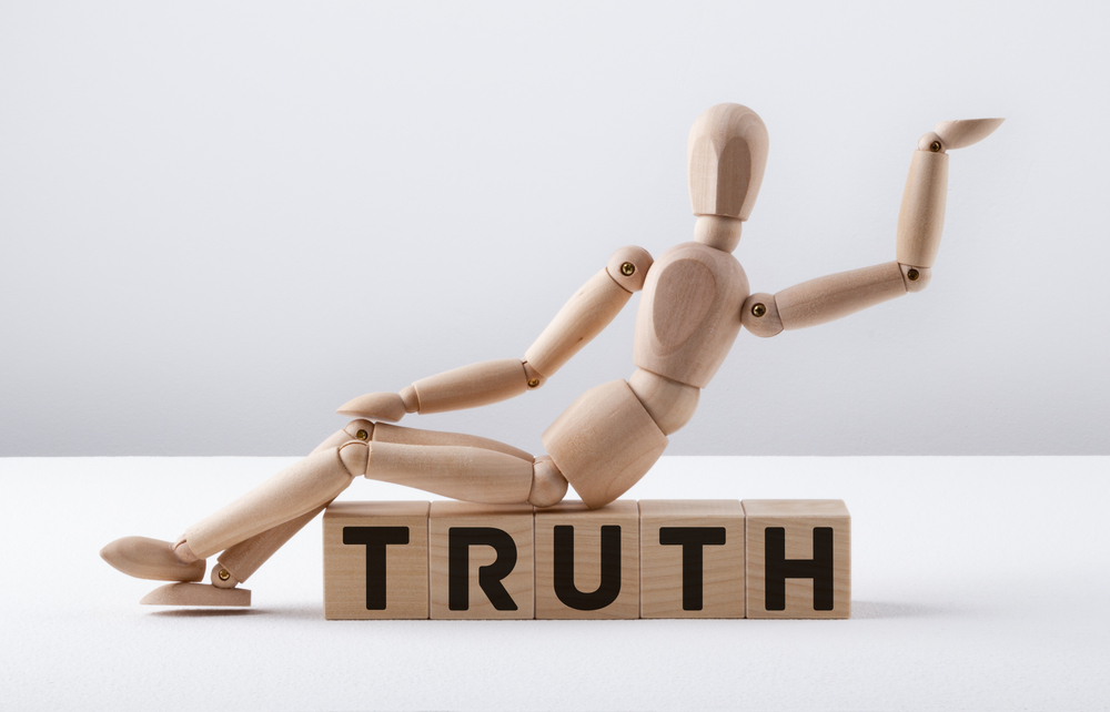 Wooden man sits on the word Truth in block letters