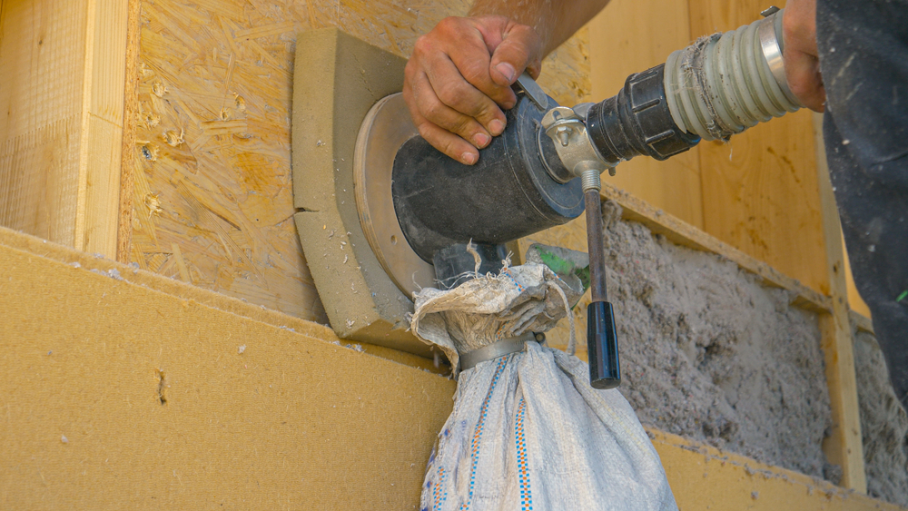 Building installing blow-in insulation with a hose in a wall